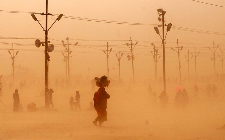 Indian Hindu devotees walk through a dust storm at the Sangam after taking a holy dip at the confluence of the rivers Ganges, Yamuna and mythical Saraswati during the Maha Kumbh festival in Allahabad on February 5, 2013. (Sanjay Kanoji/AFP/Getty Images)