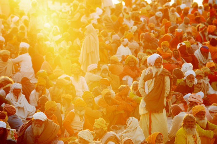 Hindu devotees gather in the shore of the confluence of the Yomuna and the Ganges river at the Sangam in the late afternoon as they wait to be served a free meal organized by an ashram during the Maha Kumbh festival in Allahabad on February 7, 2013. The Kumbh Mela in the town of Allahabad will see up to 100 million worshippers gather over 55 days to take a ritual bath in the holy waters, believed to cleanse sins and bestow blessings. (Roberto Schmidt/AFP/Getty Images)