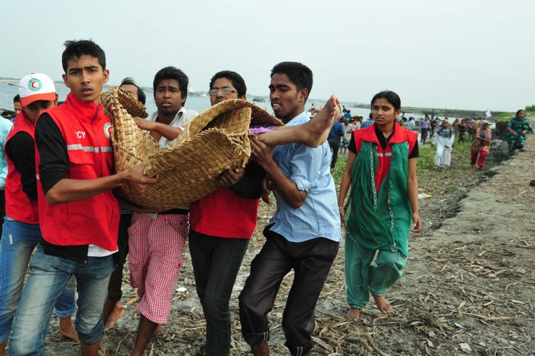 Bangladeshi rescue workers carry the dead body of a drowned passenger after a ferry accident in Munshiganj. Scores of people were missing after a ferry carrying around 100 passengers sank following a collision on a river in Bangladesh Friday, the latest in a series of disasters blamed on lax safety standards. (STR/AFP/Getty Images)