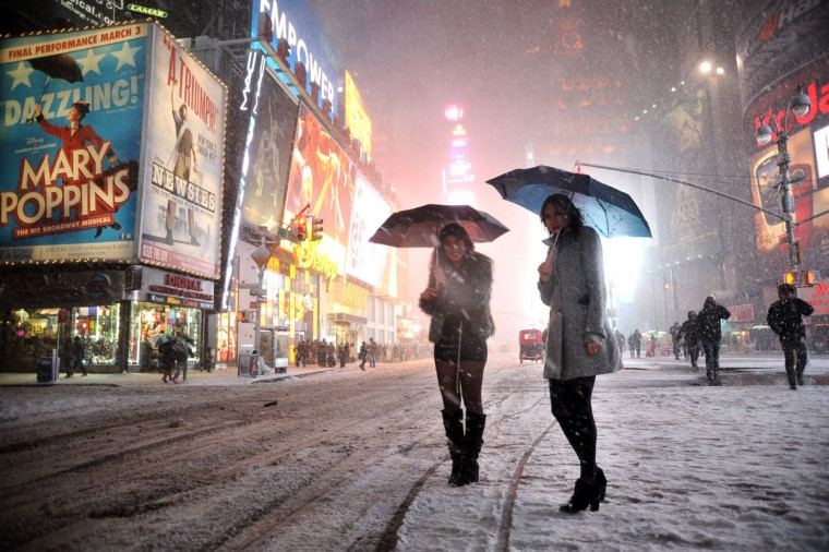 Two girls look for a taxi in the snow in Times Square in New York on February 8, 2013 during a storm affecting the northeast U.S. (Mehdi Taamallah/AFP/Getty Images)