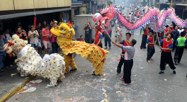Performers perform a lion dance (L) and a dragon dance on the eve of the Chinese Lunar New Year of the Snake, in China town in Manila on February 9, 2013. The Dragon Dance is usually performed during the Chinese New Year to bring in good luck and prosperity as billions of Chinese world wide celebrate Lunar New Year of the Snake on February 10. (Jay Directo/AFP/Getty Images)