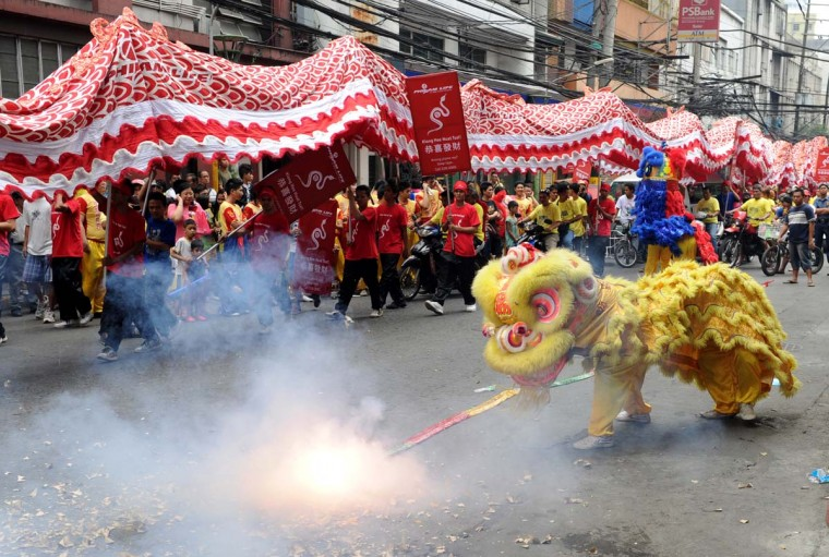 Performers perform a lion dance (front) and a dragon dance on the eve of the Chinese Lunar New Year of the Snake, in China town in Manila on February 9, 2013. The Dragon Dance is usually performed during the Chinese New Year to bring in good luck and prosperity as billions of Chinese world wide celebrate Lunar New Year of the Snake on February 10. (Jay Directo/AFP/Getty Images)