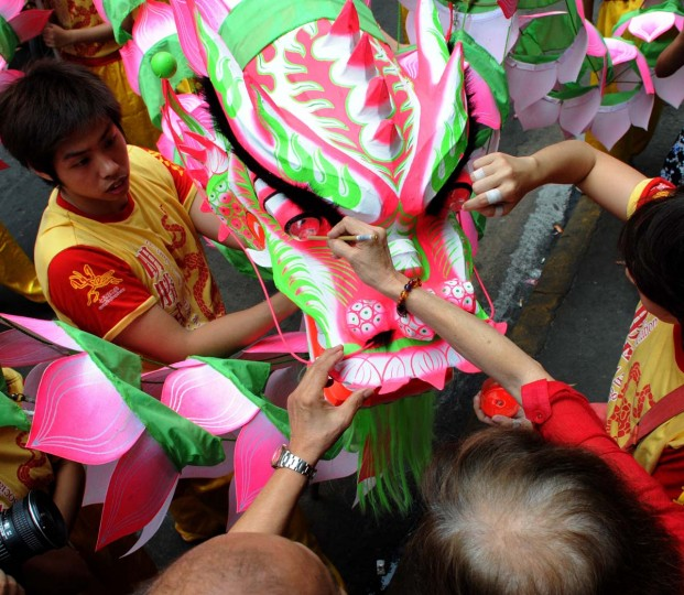 Chinese elders apply eyelids to a newly made lotus dragon during a blessing on the eve of the Chinese Lunar New Year of the Snake in the streets of China town in Manila on February 9, 2013. The Dragon Dance is usually performed during