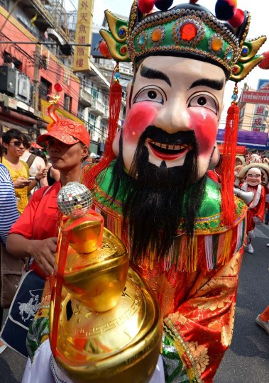 A Thai-Chinese man dressed as a God of Fortune, parades to celebrate the Chinese New Year in Bangkok's China town on February 10, 2013. Chinese communities worldwide are welcoming the ' Year of the Snake '. (Pornchai Kittiwongsakul/AFP/Getty Images)