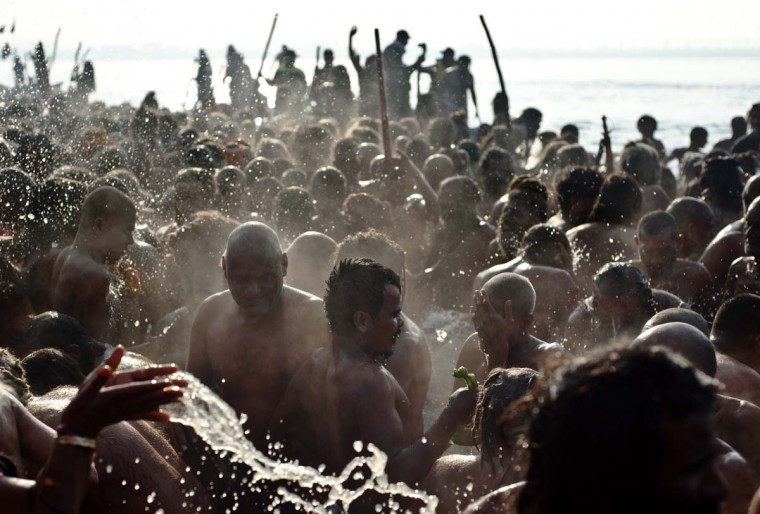 Devotees take a holy dip in the waters of Sangam or confluence of the Yamuna, Ganges and mythical Sarawati rivers on the auspicious day of 'Mauni Amavasya' during the Maha Kumbh festival in Allahabad on February 10, 2013. Tens of millions of Hindus gathered Sunday for a holy bath in India's sacred river Ganges on the most auspicious day of the world's largest religious festival.Ash-smeared naked saints led the ritual bathing before dawn -- which is said to cleanse pilgrims of their sins -- with millions following them into the swirling river waters at the festival site in Allahabad in northern India. (Manan Vatsyana/AFP/Getty Images)