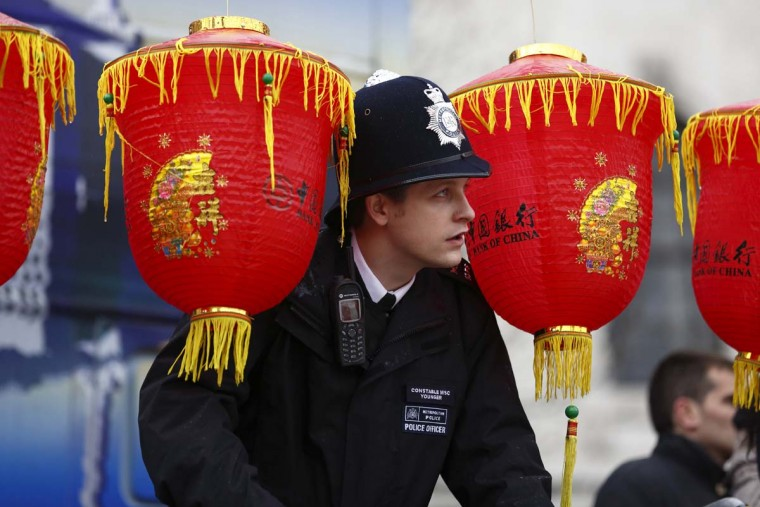 A British police officer peers through lanterns as performers in Trafalgar Square celebrate Chinese New Year in London on February 10, 2013. Chinese communities world wide traditionally welcomed in the 'Year of the Snake'. (Justin Tallis/AFP/Getty Images)