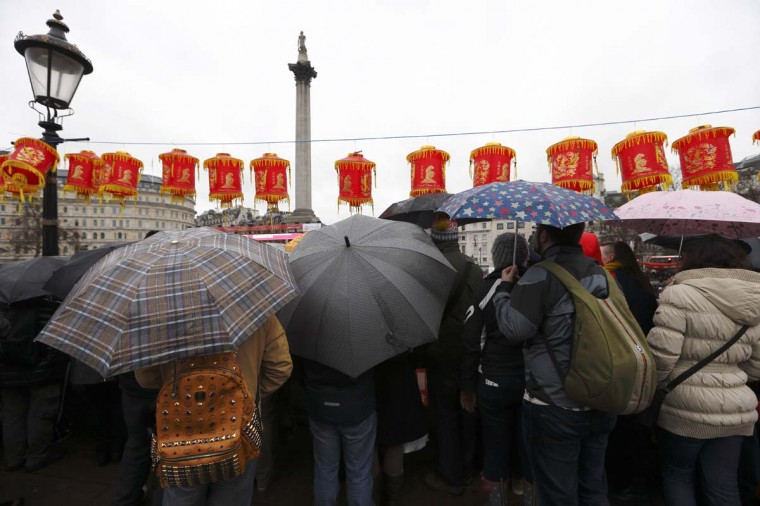 A crowd of people shelter from the rain under umbrellas as they stand and watch performers in Trafalgar Square celebrating Chinese New Year in central London on February 10, 2013. Chinese communities world wide traditionally welcomed in the 'Year of the Snake'. (Justin Tallis/AFP/Getty Images)