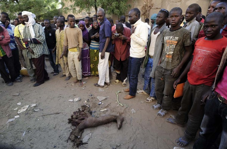 Malian people stand by the remain of a suicide bomber who blew himself up the day before in front of a police station in the northern Mali's largest city of Gao, on February 11, 2013. France bombed an Islamist hideout today in Gao, where troops rattled by guerrilla attacks intensified a security lock-down as the French-led campaign against the extremists entered its second month. (Pascal Guyot/AFP/Getty Images)