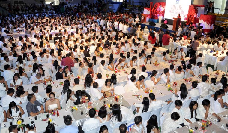 Couples take part in a mass wedding in Manila on February 14, 2013. Some 400 couples exchanged vows inside a packed gymnasium on the outskirts of Manila's Makati financial district, as a school band played love songs that drowned out the heavy traffic outside. (Jay Directo/AFP/Getty Images)