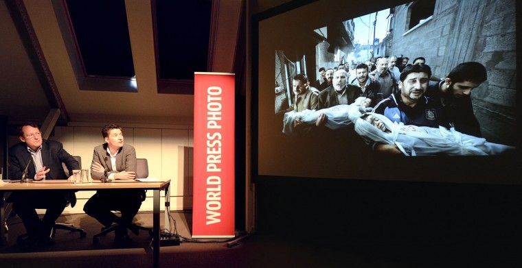 World Press Photo jury president Santiago Lyon (L) and Managing Director of World Press Photo Michael Munneke look at the contest's winning photo during the annoucement of it in Amsterdam on February 15, 2013. Photographer Paul Hansen from Sweden won the 56th World Press Photo Contest with a picture of men carrying the bodies of two dead children in Gaza City. (Lex van Lieshout/AFP/Getty Images)