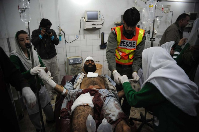 Pakistani paramedics treat an injured victim after the militants' attack on the office of the top political official of Khyber tribal region in Peshawar on February 18, 2013. Militants including a suicide bomber attacked the office of a senior official in Pakistan's northwestern city of Peshawar on Monday, killing five people, officials said. (Hasham Ahmed/AFP/Getty Images)