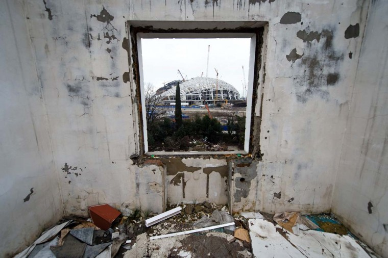 The Central Stadium for the Winter Olympics 2014 is seen through the window of a derelict house in Sochi on February 18, 2013. With a year to go until the Sochi 2014 Winter Games, construction work and development continues as Olympic tests events and World Championship competitions are underway. (Leon Neal/AFP/Getty Images)