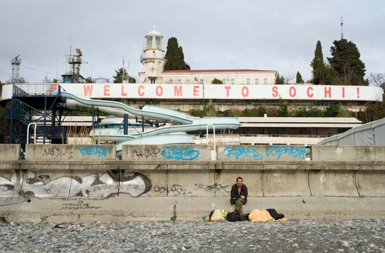 "A man sits among his belongings on the beachfront beneath a large ""Welcome to Sochi!"" sign in central Sochi on February 18, 2013. With a year to go until the Sochi 2014 Winter Games, construction work and development continues as Olympic tests events and World Championship competitions are underway. (Leon Neal/AFP/Getty Images)"