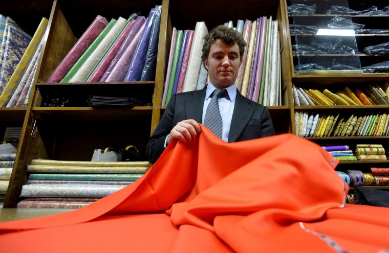 An employee holds the red cloth which is used to make a cardinal's vestment at Gammarelli ecclesiastical tailoring in Rome on February 21, 2013. The tailors are expected to be already creating sumptuous vestments for the new pope in small, medium and large sizes so that whoever is chosen will fit right into the clothes. (Alberto Pizzoli/AFP/Getty Images)