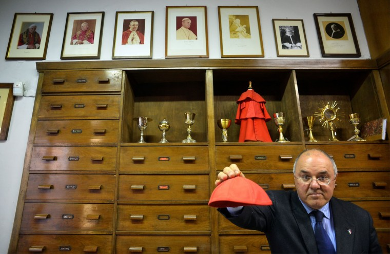 An employee holds up a red cardinal's zucchetto at Gammarelli ecclesiastical tailoring in Rome on February 21, 2013. The tailors are expected to be already creating sumptuous vestments for the new pope in small, medium and large sizes so that whoever is chosen will fit right into the clothes. (Alberto Pizzoli/AFP Getty Images)