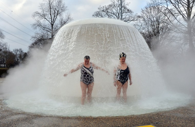 "Two women stand under a fountain in the so-called ""Sonnenbad"" (Sun bath) swimming pool at temperatures just below 0 degrees Celsius during the opening of the pool for the new season Karlsruhe, southern Germany. The pool is the first to re-open after being closed for winter. (Uli Deck/AFP/Getty Images)"