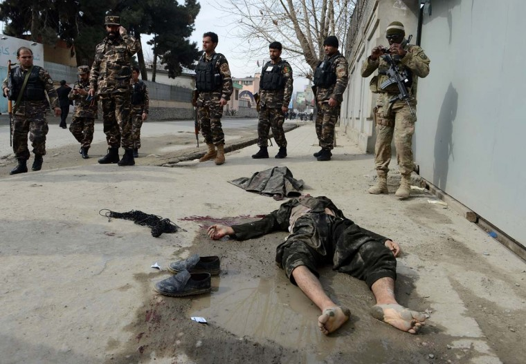 A U.S. soldier and Afghan security forces stand alongside the body of a suspected suicide bomber in Kabul on February 24, 2013. Afghan security forces on February 24 shot dead one suspected suicide bomber in a car near a construction site in Kabul's diplomatic enclave, a police official and an AFP photographer said. (Shah Marai/AFP/Getty Images)