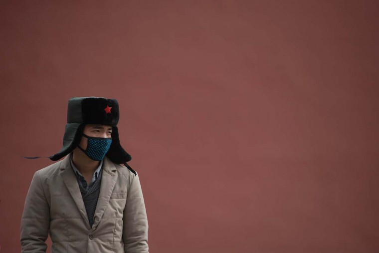 A man wearing face mask stands before a wall inside the Forbidden City during heavy pollution in Beijing on February 28, 2013. Beijing residents were urged to stay indoors as pollution levels soared before a sandstorm brought further misery to China's capital. (Ed Jones/AFP/Getty Images)
