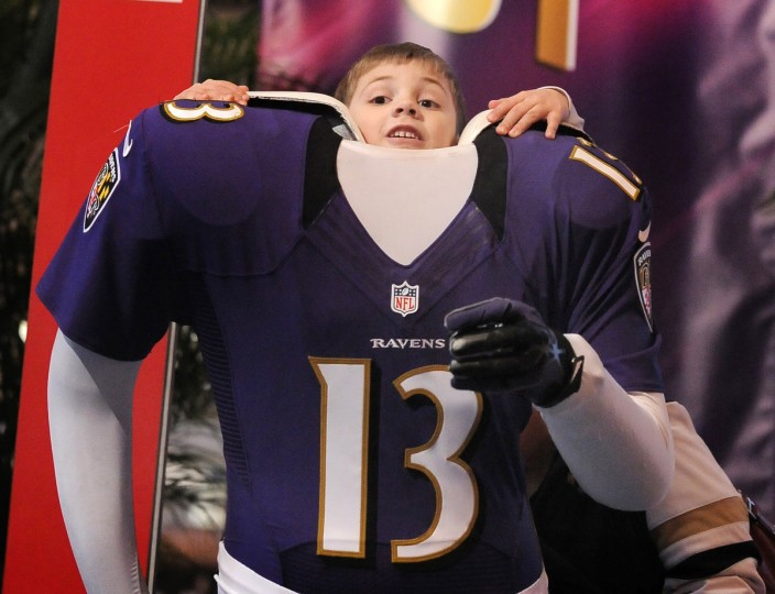 Six year old Jack Bazile tries to fit into a Ravens player cut out, at the NFL's Fan Experience in New Orleans. (Gene Sweeney Jr./Baltimore Sun)