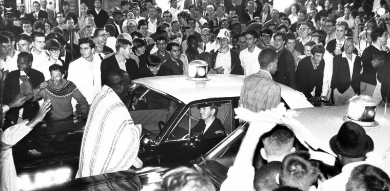 October 10, 1966 — Jubilant Orioles fans around Baltimore Street as police car squeezes through. Many began rocking the car, but the officer kept smiling all the time. (William L. LaForce/Baltimore Sun)