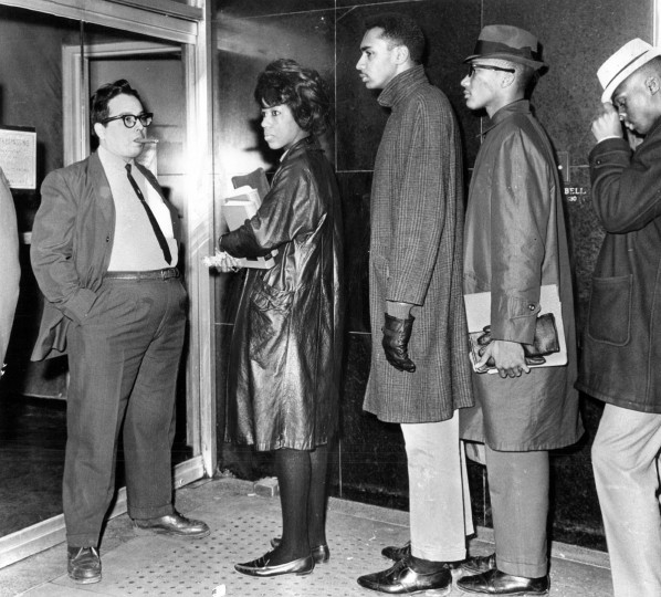 Feb. 19, 1963: A man blocks the entrance to the Northwood Theater where about 150 members of the Civic Interest Group demonstrated last night. All were arrested and charged with trespassing and disorderly conduct during the protest against segregation at the theater. -- This photo was published under the headline 'DOORS BARRED.' (William L. LaForce/Baltimore Sun)