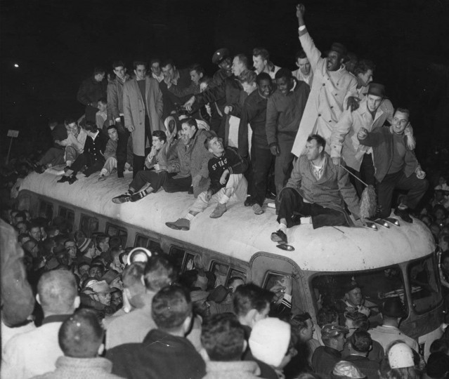 Dec. 29, 1958 — A huge crowd of 30,000 estimated fans greeted the Baltimore Colts as they arrived at Friendship International Airport. Pictured, a group of fans ride atop the bus carrying the Colt players as it begins to ride through their welcomers. The Colts won the National Football League Championship with a thrilling 23-17 sudden death victory over the New York Giants in Yankee Stadium. (Associated Press File Photo)
