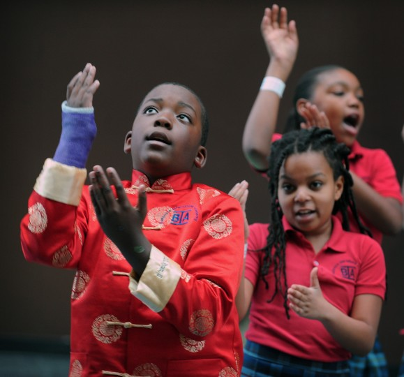 Dontae Ryan II, 9, a fourth grader at the Baltimore International Academy, dressed in a traditional Chinese new year coat, sings in Mandarin Chinese while performing new year song and dance with classmates at Port Discovery. (Kenneth K. Lam/Baltimore Sun)