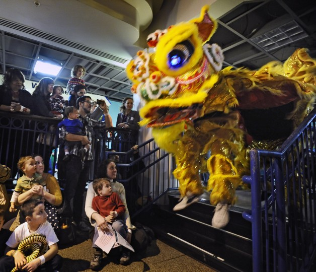 A lion dancer performer jumps down steps as children and parents watch on during the celebration of Chinese New Year at Port Discovery Children's Museum. (Kenneth K. Lam/Baltimore Sun)