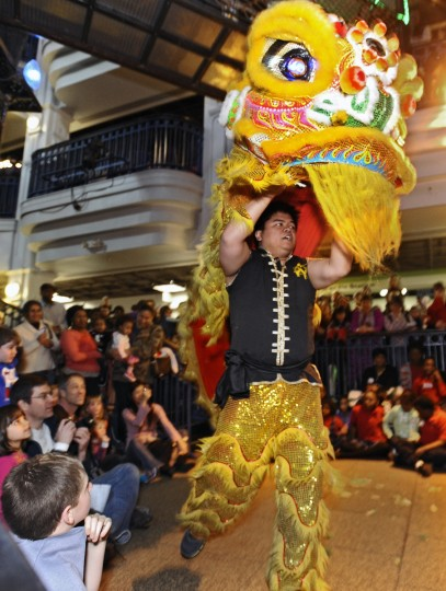 A dance performer lifts the head of the lion over his head as children and parents watch on during the celebration of Chinese New Year. The lion or dragonÕs head, made out of bamboo and paper-m‰chŽ, can weight from 15 to 50 pounds. (Kenneth K. Lam/Baltimore Sun)