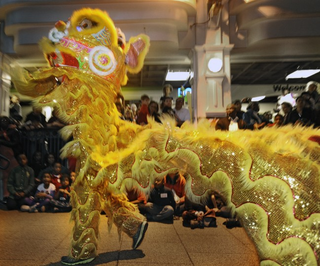 A dance performer entertains the crowd at Port Discovery Children's Museum. To warn off evil spirits, the lion dance, accompanied by the playing of drum and cymbals, is performed in front of homes or at the place of work. The mythical lion represents vitality, prosperity and good fortune. (Kenneth K. Lam/Baltimore Sun)