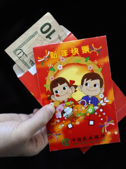 "Red envelopes, called ""hong bao"" in Mandarin, filled with money typically given to children or unmarried adults with no job during new year or special occasions such as birthdays. These pictured are specially for children and wishing them ""Happy New Year."" The color red denotes good fortune and abundance in Chinese Culture. (Kenneth K. Lam/Baltimore Sun)"