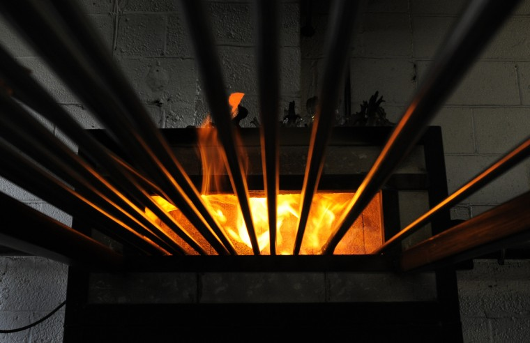 A 1200 degree pipe warmer is used to keep the blowpipes hot before they are used for glass blowing. (Lloyd Fox/Baltimore Sun)