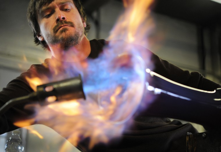 Tim McFadden a professional glassblower uses a torch on the end of a vase he has made to create a shine on the inside of the vase. Using the torch also helps to reduce the interior color. (Lloyd Fox/Baltimore Sun)