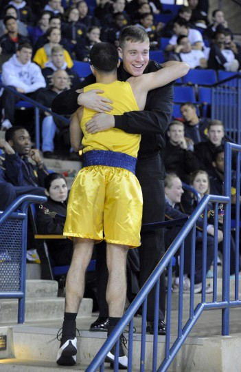 Midshipman Robert Volm, facing camera, hugs Jim Lawson after Lawson's victory in the 139 pound weight class. (Lloyd Fox/Baltimore Sun)
