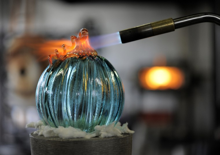 A torch is used on a glass pumpkin that is made by McFadden. (Lloyd Fox/Baltimore Sun)