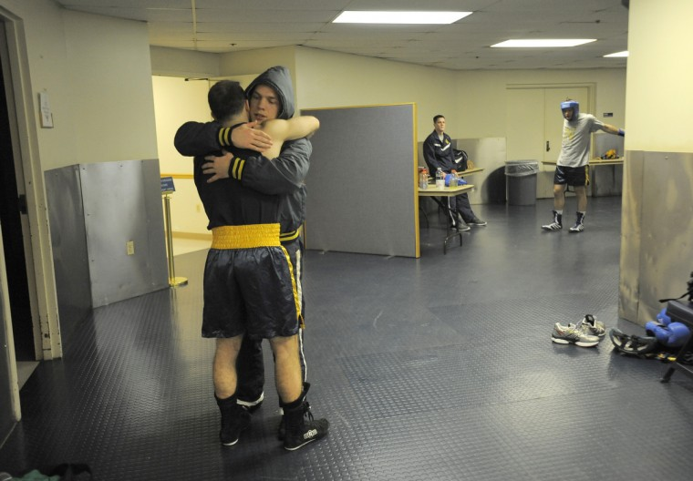 Midshipman Mike Mourafetis, left, gets a hug from a teammate after winning his 147 pound bout. (Lloyd Fox/Baltimore Sun)