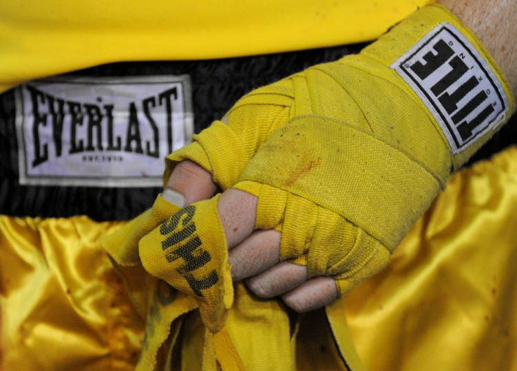 Beau Haworth takes off the wrap on his hands after he was defeated by fellow midshipman Matt Brewer in the heavyweight division. (Lloyd Fox/Baltimore Sun)