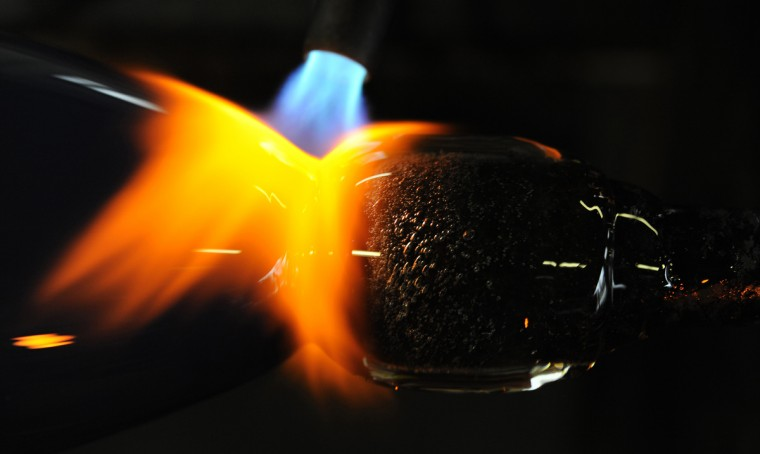 A blowtorch is used to help fuse two pieces of glass together. (Lloyd Fox/Baltimore Sun)