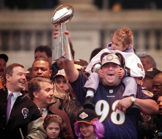 January 30, 2001 — Tony Siragusa holds the Lombardi Trophy along with his daughter, Samantha Rose, as Martin O'Malley, left, looks on. The were celebrating at the rally following the Ravens' victory parade. (David Hobby/Baltimore Sun)
