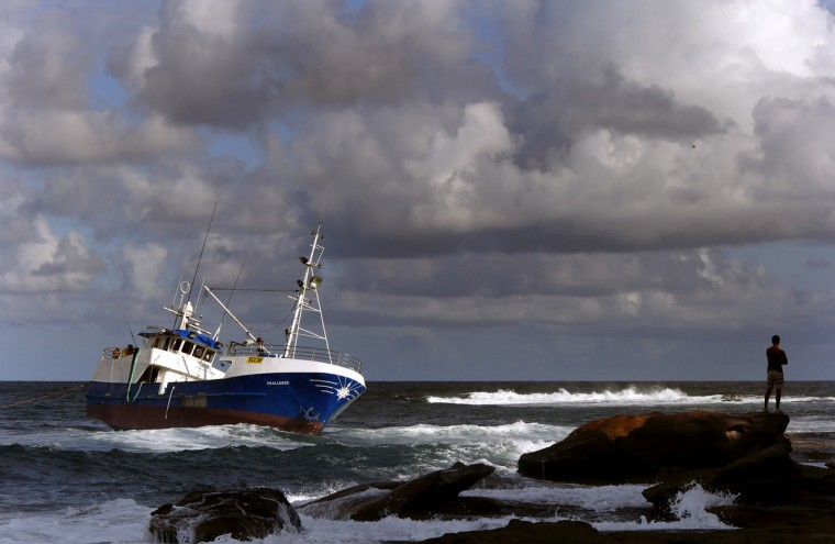 A man stands atop a rock as he looks at a fishing trawler that ran aground at Sydney's Cronulla Beach. Attempts to remove the trawler have so far been unsuccessful after it ran aground early on Monday morning, with four crewmen, all from Indonesia, being rescued, local media reported. (David Gray/Reuters)