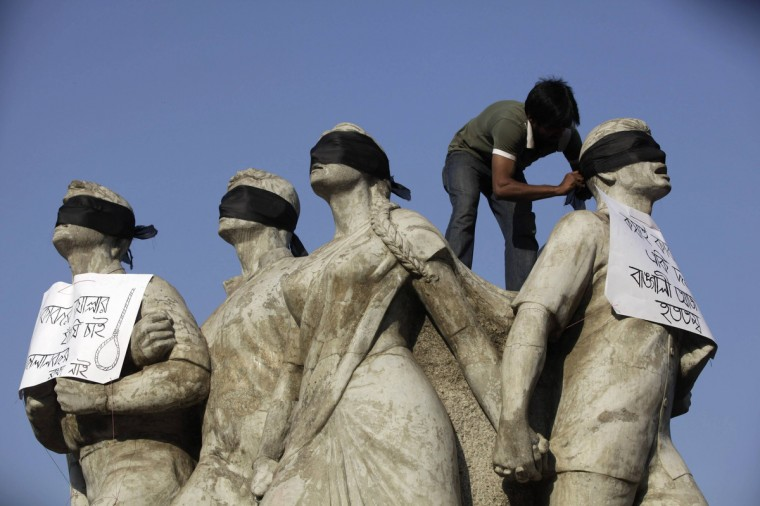 A student activist puts black scarves on the eyes of Shoparjito Shadhinota, a sculpture that represented all sections of people in Bangladesh's liberation War in 1971, demanding capital punishment for Bangladesh's Jamaat-e-Islami senior leader Abdul Quader Mollah, after a war crimes tribunal sentenced him to life imprisonment, in the campus of University of Dhaka. The war crimes tribunal sentenced Quader Mollah, 64, to life in prison on Tuesday, the second verdict in trials that have reopened wounds about the country's independence war and sparked riots. He was found guilty of charges including murder, rape, torture and arson during Bangladesh's war to break away from Pakistan in 1971. (Andrew Biraj/Reuters)