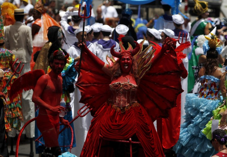 "Revellers wearing devil costumes perform during an annual block party known as ""Escravos da Maua"", one of the many carnival parties to take place in the neighbourhoods of Rio de Janeiro February 3, 2013. (Pilar Olivares/Reuters)"