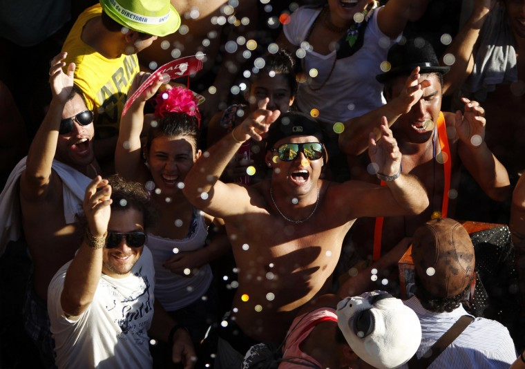 "Water is sprinkled on revellers to help them cool off during an annual block party known as ""Ceu na Terra"" (or Sky on Earth), one of the many carnival parties to take place in the neighbourhoods of Rio de Janeiro February 2, 2013. (Pilar Olivares/Reuters)"
