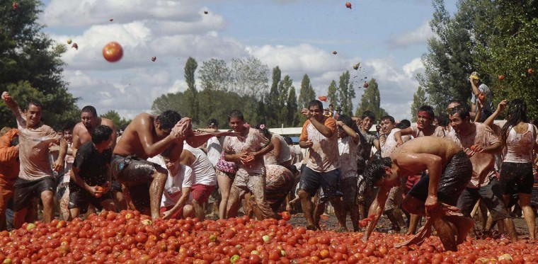 "Revellers play with tomatoes during a ""Tomatina"" (tomato fight) in Quillon town near Concepcion city, south of Santiago February 16, 2013. (Jose Luis Saavedra/Reuters)"