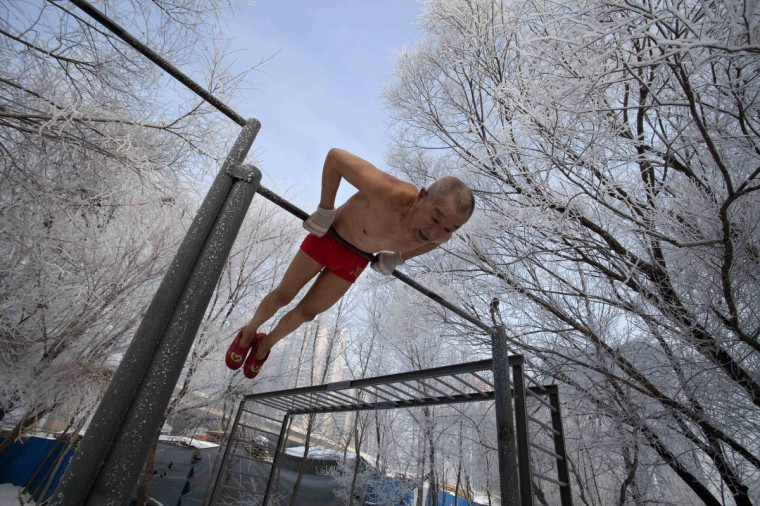 Gao Yinyu, 77, does his morning exercise before swimming in Songhua river in Jilin, Jilin province. Gao said he exercises everyday irrespective of the weather to keep himself fit since he retired as a teacher a few years ago. (Reuters)