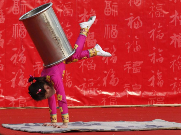 A girl performs an acrobatic show during the temple fair in Ditan Park, also known as the Temple of Earth, in Beijing February 9, 2013. The Lunar New Year, or Spring Festival, begins on February 10 and marks the start of the Year of the Snake, according to the Chinese zodiac. (Kim Kyung-Hoon/Reuters)
