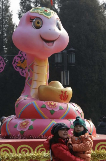 A mother holding her child poses for a photo next to a snake sculpture at a temple fair to celebrate the Chinese Lunar New Year at Ditan Park (the Temple of Earth), in Beijing, February 9, 2013. The Lunar New Year, or Spring Festival, begins on February 10 and marks the start of the Year of the Snake, according to the Chinese zodiac. (Jason Lee/Reuters)