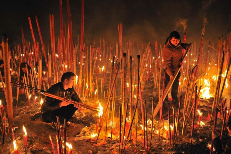 Worshippers burn incense to pray for good fortune on the first day of the Chinese Lunar New Year at Dafo temple in Chongqing municipality February 10, 2013. The Lunar New Year, or Spring Festival, begins on February 10 and marks the start of the Year of the Snake, according to the Chinese zodiac. (Reuters)