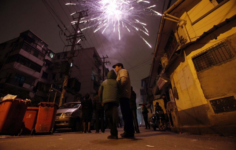 People watch as fireworks light up the skyline of Shanghai in celebrations of Chinese New Year, in Shanghai February 9, 2013. The Lunar New Year, or Spring Festival, begins on February 10 and marks the start of the Year of the Snake, according to the Chinese zodiac. (Carlos Barria/Reuters)