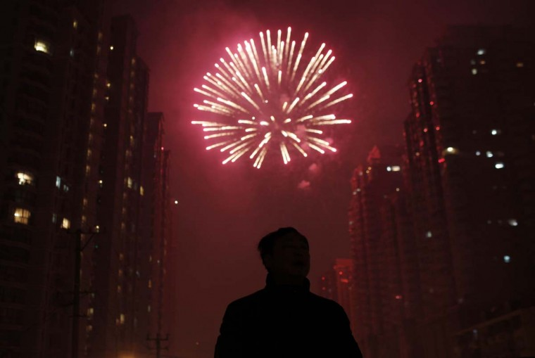 A man watches as fireworks light up the skyline of Shanghai in celebration of Chinese New Year in Shanghai early February 10, 2013. The Lunar New Year, or Spring Festival, begins on February 10 and marks the start of the Year of the Snake, according to the Chinese zodiac. (Carlos Barria/Reuters)